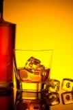 Vidro do uísque com os cubos de gelo perto da garrafa na tabela com reflexão, atmosfera morna do matiz Fotos de Stock Royalty Free