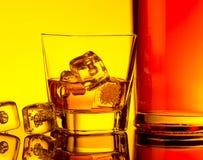 Vidro do uísque com os cubos de gelo perto da garrafa na tabela com reflexão, atmosfera morna do matiz Fotografia de Stock
