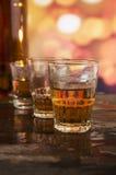 Vidro do uísque do rum sobre luzes defocused Imagens de Stock Royalty Free