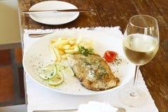 Vidro do vinho branco com peixes e microplaquetas imagens de stock royalty free