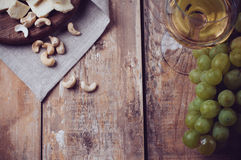Vidro do vinho branco, das uvas, das porcas de caju e do queijo macio Imagem de Stock