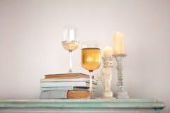 Vidro do vinho branco, de um livro e de duas velas no armário Imagem de Stock Royalty Free