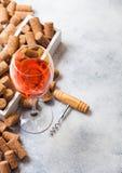 Vidro do vinho cor-de-rosa cor-de-rosa com a caixa das corti?a e o abridor do corkscrew no fundo de pedra da mesa de cozinha Vist fotos de stock