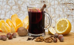 Vidro do vinho, do limão, da laranja e de porcas ferventados com especiarias na tabela de madeira Foto de Stock Royalty Free