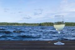 Vidro do vinho em um cais de madeira Conceito das férias do recurso luxuoso Lago azul e fundo verde da floresta Imagens de Stock