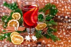 Vidro do vinho ferventado com especiarias com decoração festiva Fotografia de Stock