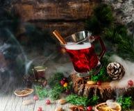 Vidro do vinho ferventado com especiarias quente pelo ano novo com os ingredientes para o cozimento, as porcas e as decorações do fotografia de stock