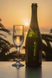 Vidro do vinho no nascer do sol no mar Imagens de Stock Royalty Free