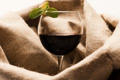 Vidro do vinho tinto com pano de saco no fundo fotografia de stock royalty free
