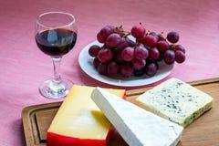 Vidro do vinho tinto, de uvas vermelhas doces na placa branca e de tipos da árvore de queijo na placa de corte de madeira marrom  foto de stock royalty free