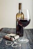 Vidro do vinho tinto e de um presente em um fundo de madeira fotografia de stock royalty free