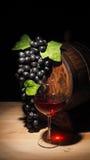 Vidro do vinho tinto e do tambor na tabela de madeira Imagens de Stock
