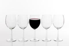 Vidro do vinho tinto em seguido de vidros vazios Imagens de Stock Royalty Free