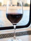 Vidro do vinho tinto no peitoril da janela do barco do cruzeiro foto de stock