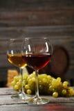 Vidro do vinho vermelho e branco, dos queijos e das uvas no fundo de madeira cinzento Fotografia de Stock Royalty Free