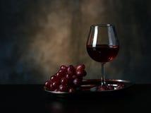 Vidro do vinho vermelho e de uvas vermelhas Fotografia de Stock Royalty Free