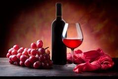 Vidro do vinho vermelho e do frasco com uvas Imagem de Stock Royalty Free