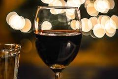 Vidro do vinho vermelho na frente da árvore de Natal fotografia de stock royalty free