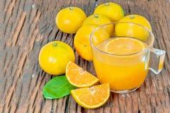 Vidro dos sucos de laranja com algumas partes de laranjas na madeira Foto de Stock