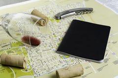 Vidro e corti?a de vinho no mapa para o planeamento da rota Caderno preto para notas imagem de stock