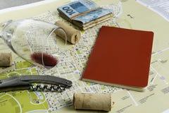 Vidro e corti?a de vinho no mapa para o planeamento da rota Caderno vermelho para notas foto de stock