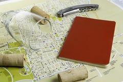 Vidro e corti?a de vinho no mapa para o planeamento da rota Caderno vermelho para notas fotos de stock royalty free