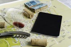 Vidro e corti?a de vinho no mapa para o planeamento da rota Livro de nota preto para notas e notas imagem de stock