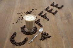 Vidro e feijões do copo de café Imagem de Stock