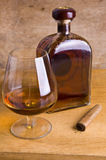 Vidro e frasco do conhaque no fundo de madeira Fotografia de Stock