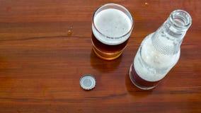 Vidro e garrafa da cerveja com o tampão de garrafa openned na tabela de madeira Imagens de Stock Royalty Free
