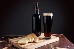 Vidro e garrafa da cerveja escura com queijo fumado no varrão do corte Fotografia de Stock