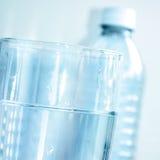 Vidro e garrafa de água desobstruídos azuis de água Fotos de Stock