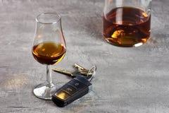Vidro e garrafa do uísque em um tampo da mesa de pedra e em chaves do carro Condução na embriaguez foto de stock royalty free