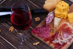 Vidro e garrafa do vinho tinto, do queijo, do salame, das nozes, do prosciutto e dos alecrins no fundo de madeira Imagens de Stock