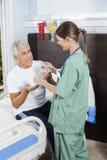 Vidro e medicina pacientes de água da recepção da enfermeira fêmea Fotos de Stock Royalty Free