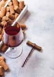 Vidro elegante do vinho tinto com a caixa das corti?a e o abridor no fundo de pedra da mesa de cozinha foto de stock royalty free