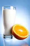 Vidro fresco do leite e metade da laranja suculenta Imagem de Stock Royalty Free