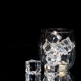 Vidro isolado no fundo preto com cubos de gelo Fotos de Stock Royalty Free