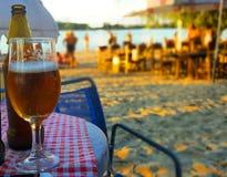 Vidro meio cheio da cerveja na praia durante o dia de verão ensolarado Imagem de Stock