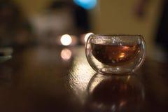 Vidro pequeno transparente do chá preto chinês em uma tabela, tiro co imagem de stock royalty free