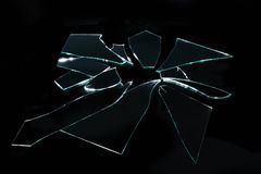 Vidro quebrado com partes afiadas no fundo preto Imagens de Stock