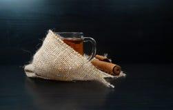Vidro quente do copo de chá em um dia do outono/inverno com canela e serapilheira/juta em um fundo preto imagens de stock royalty free