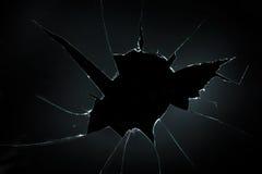 Vidro rachado quebrado com furo grande sobre o fundo preto Fotografia de Stock Royalty Free