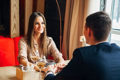 Vidro romântico da bebida da data dos pares felizes novos do vinho branco no restaurante, comemorando o dia de são valentim Foto de Stock Royalty Free
