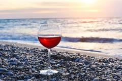 Vidro romântico do vinho que senta-se na praia no por do sol colorido, vidro do vinho tinto contra o por do sol, vinho tinto na p Fotografia de Stock Royalty Free