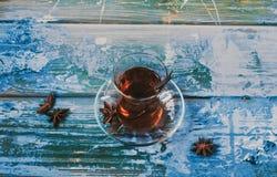 Vidro turco tradicional da tulipa com chá preto no fundo de madeira azul com anises fotografia de stock