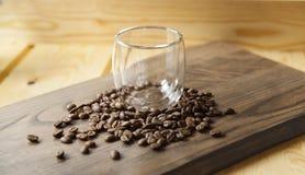 Vidro vazio com feijões de café ao redor em uma tabela de madeira fotografia de stock