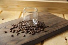 Vidro vazio com feijões de café ao redor em uma tabela de madeira fotografia de stock royalty free