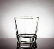 Vidro vazio do uísque na tabela preta com reflexão no fundo branco Fotografia de Stock