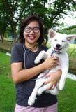 Vidro vestindo da mulher asiática usando o estetoscópio com o cachorrinho exterior fotografia de stock royalty free